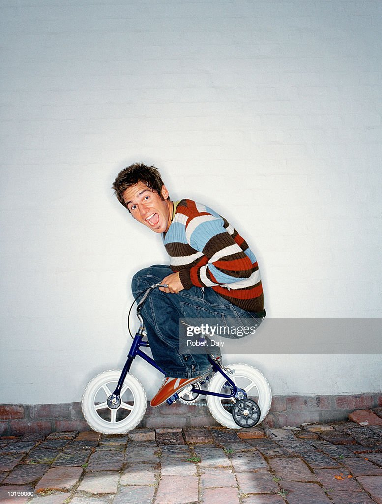 Man riding child's bicycle with stabilisers, mouth open, portrait