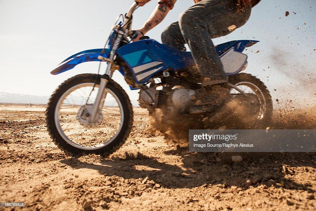 Man riding dirt bike in desert