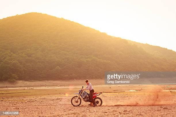 Man riding dirt-bike in dress shirt and pants