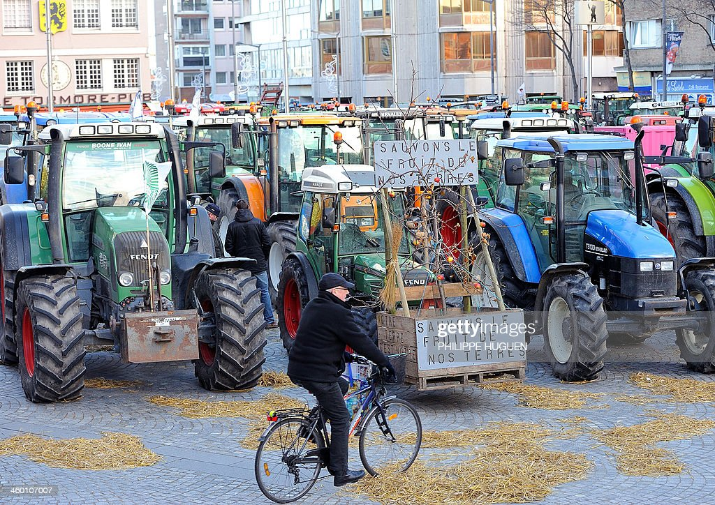 A man riding his bicycle passes by tractors blocking the road on January 2, 2014 in Dunkerque, northern France, during a demonstration by farmers called by the Gers farmers' union FDSEA to protest against the regional and ecological key measure of the Grenelle Environment, known as 'La Trame verte et bleue' (blue-green infrastructure). Sign (C) reads: 'Let us save the fruit of our earth'. AFP PHOTO / PHILIPPE HUGUEN