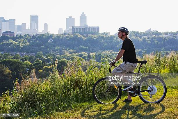Man riding his electric bicycle with Edmonton city skyline in the background