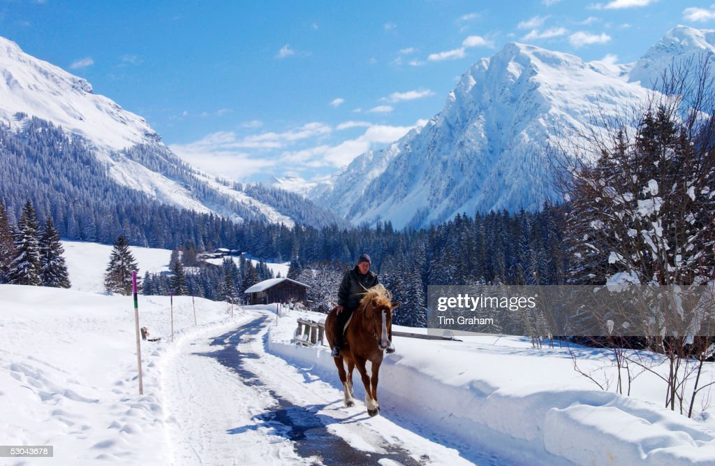 Man riding his home home at Klosters Amongst the Silvretta group of the Swiss Alps Road to SilvrettaMountain at right is PLinard 3411 metres high