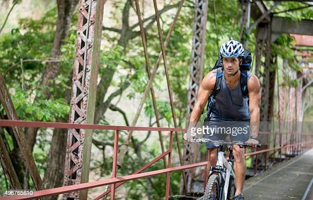 Man riding his mountain bike crossing a bridge