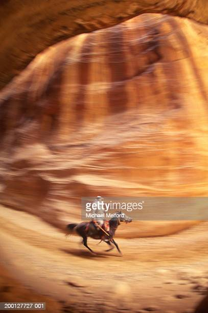 Man riding horse in canyon (blurred motion)