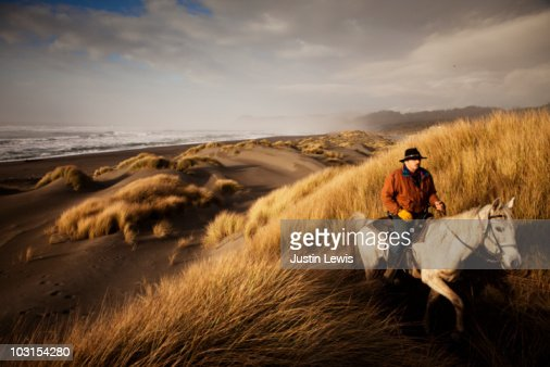 Man riding horse in sand dunes : Stock Photo