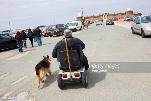 A man riding in a mobility scooter walks his Alsation Dog towards Fort Perch Rock In 1986 world famous photographer Martin Parr published his book...