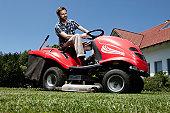 Man riding lawn mower in backyard