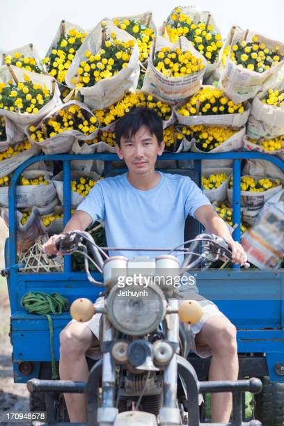 Man riding motobycyle carring flowers