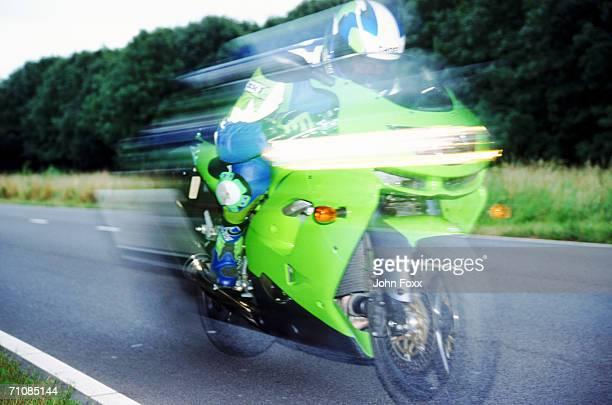 Man riding motorbike on country road (blurred motion)