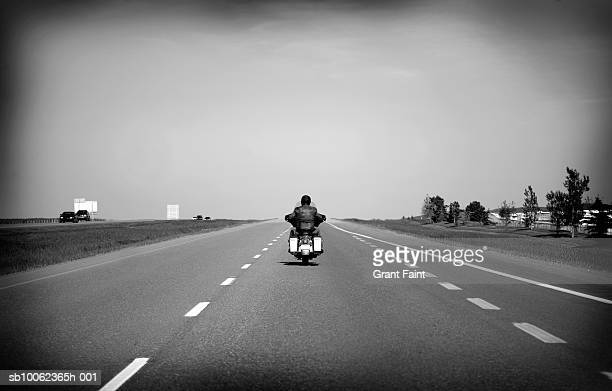 Man riding motorbike on highway, rear view