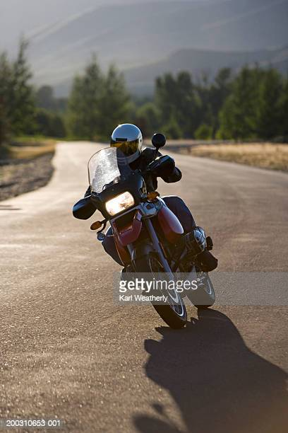 Man riding motorcycle down road