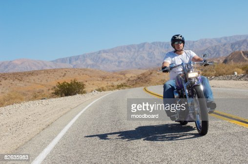 Man riding motorcycle on desert road : Stock Photo
