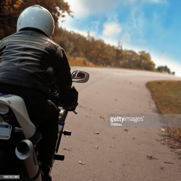 Man riding motorcycle on rural road