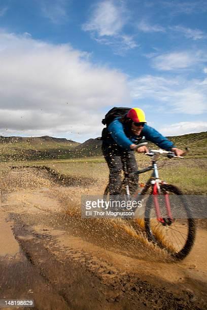 Man riding mountain bike in mud