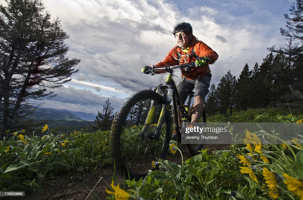 Man riding mountain bike in wildflowers