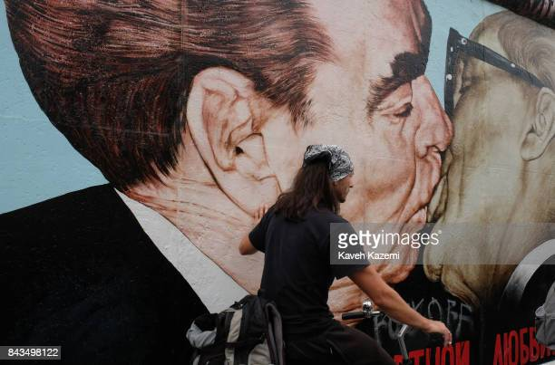 A man riding on bicycle goes past the mural depicting Leonid Brezhnev and Erich Honecker kissing painted by Dmitri Vrubel in The East Side Gallery on...