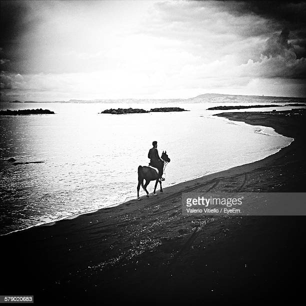 Man Riding On Horse At Beach Against Sky