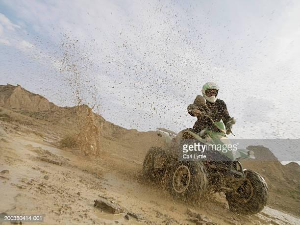 Man riding quad bike through mud