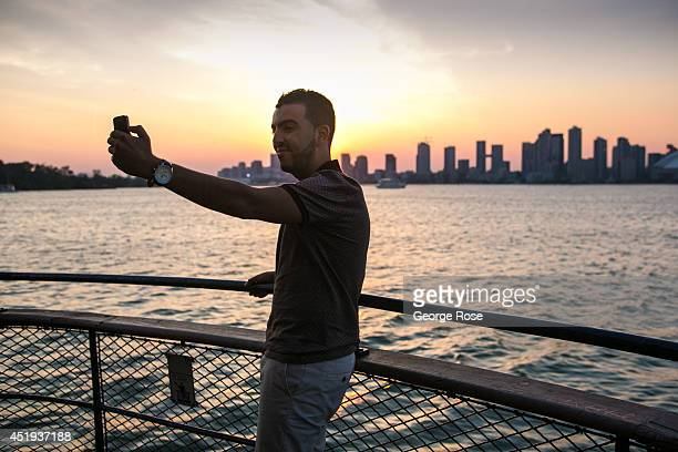 A man riding the ferry to Centre Island takes a selfie with the downtown skyline as his backdrop on June 28 2014 in Toronto Ontario Canada Canada's...