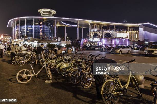 A man right uses a smartphone to unlock an Ofo Inc sharing bicycle on a street at night in Wuhan China on Tuesday June 13 2017 China's central bank...