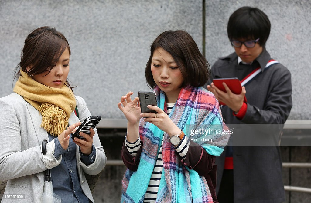 A man, right, uses a touch pad device as women use their smartphones outside a train station in Tokyo, Japan, on Sunday, April 21, 2013. The number of smartphone subscribers in Japan surged to 37 percent of all contracts as of March 31 from 3 percent three years earlier, according to Tokyo-based MM Research Institute Ltd. Photographer: Yuriko Nakao/Bloomberg via Getty Images