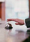 Man ringing bell for service at hotel's front desk, close-up of hand