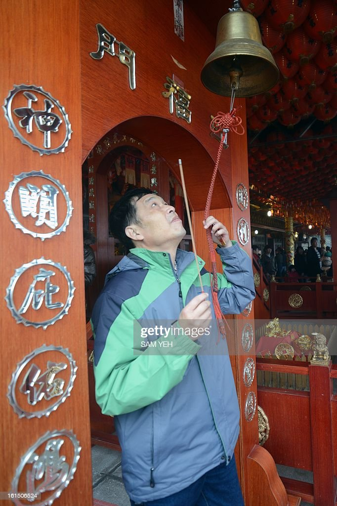 A man rings a bell for good fortune at Hongludi temple, a Taoist god of fortune, in Chunghe, the New Taipei City, on the third day of the lunar new year on February 12, 2013. Chinese lunar new year, celebrated by Chinese communities the world over, falls on February 10 with the beginning of the new moon. AFP PHOTO / Sam Yeh