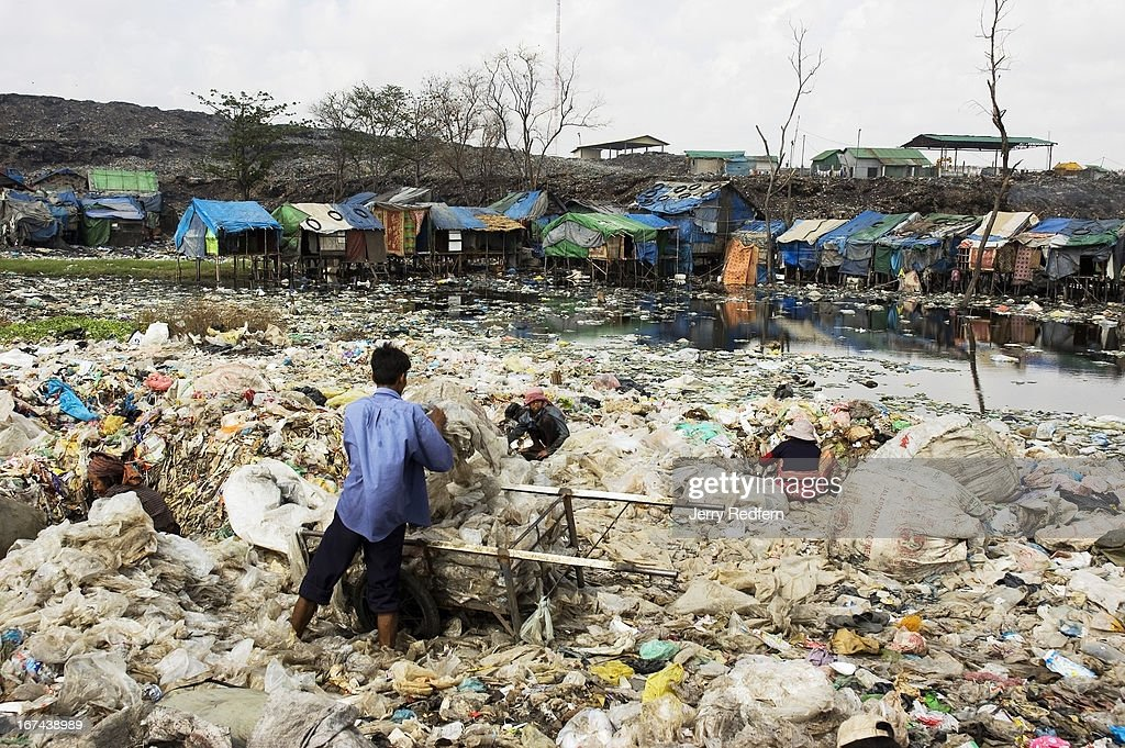 A man rinses recycled plastic bags in a sewage and garbage-filled pond on the edge of Steung Meanchey dump in Phnom Penh. Hundreds of families make their living from the dump, picking recyclable goods from the city's refuse. Dozens of families live directly atop the mountain of waste. Over the years, the dump has grown drastically, pouring into adjacent neighborhoods as those neighborhoods fill with people looking to make money from the dump. The city government has evicted the people living in the dump more than once, but people return as they have nowhere else to go..