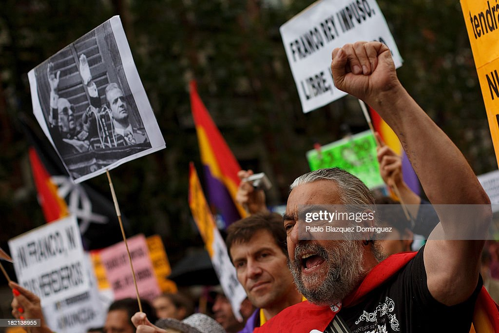 A man rise his fist and shout slogans during a demonstration against the Spanish Monarchy next to a picture showing Dictator Francisco Franco and King Juan Carlos of Spain together at Princesa Street on September 28, 2013 in Madrid, Spain. Organizers call for a demonstration on the anniversary of 'Surround the congress protest' to claim the abolition of the Monarchy. Currently King Juan Carlos of Spain is in hospital recovering from a hip operation. The Spanish Royal Family has lost popularity since the King injured his hip on elephant hunting trip and the King's son-in-law, Inaki Urdangarin is being investigated over a corruption scandal.