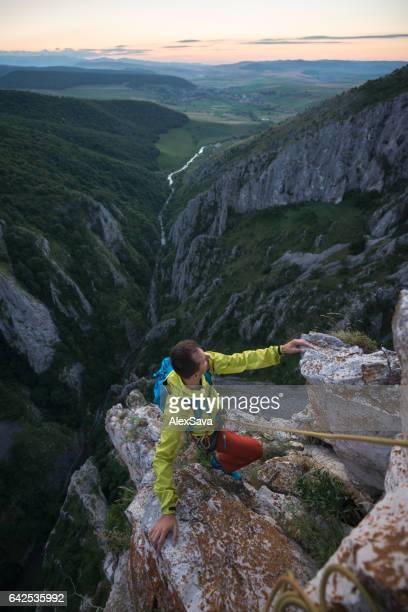 Man rock climbing on a rocky ridge during sunset