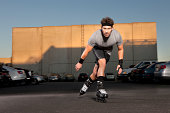 Man roller-skating in parking log, sunset