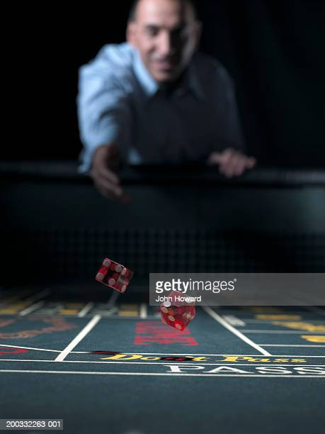 Man rolling dice at craps table (focus on falling dice)