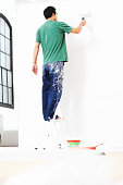 Man rolling paint on wall, rear view