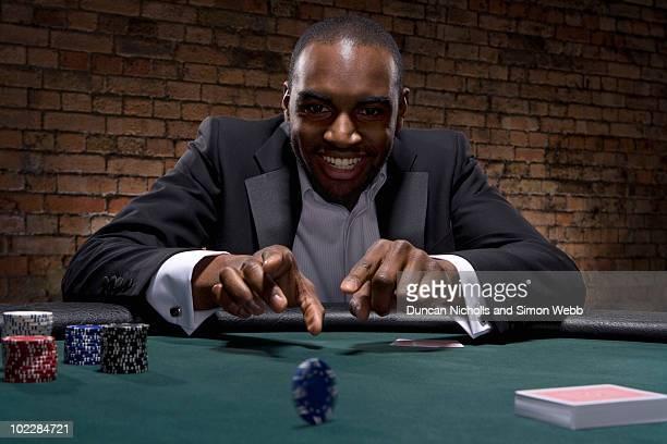 Man rolling poker chip in casino