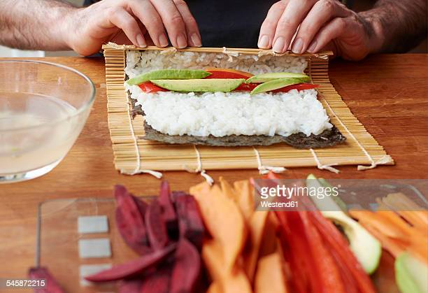 Man rolling sushi with a sweet potato, avocado and bell pepper filling