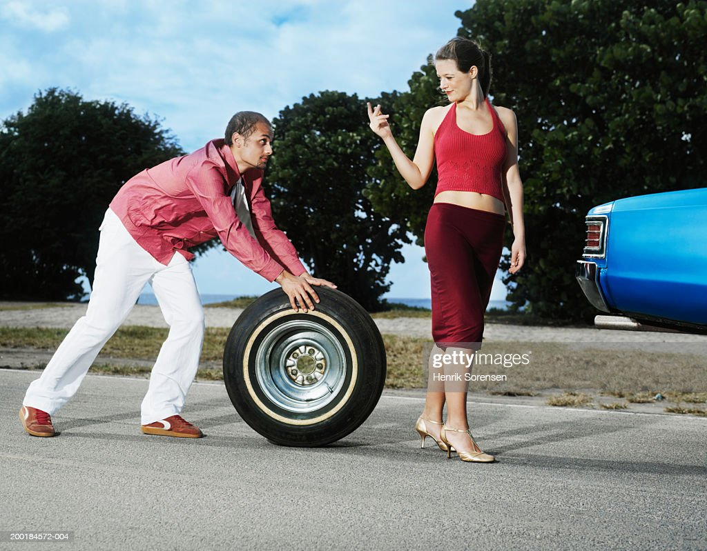Man rolling tyre, following woman beckoning with finger