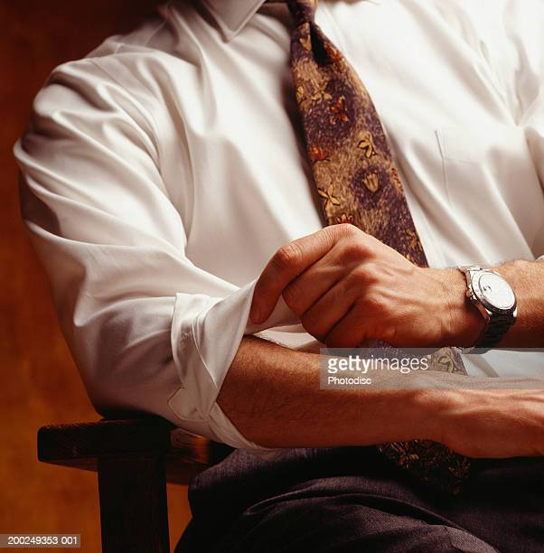 Man rolling up sleeves, (Close-up)