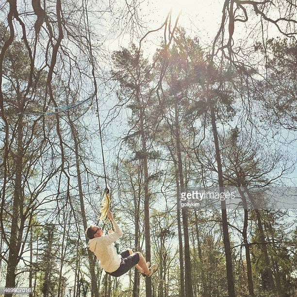 Man rope swinging from the tree in the woods, England