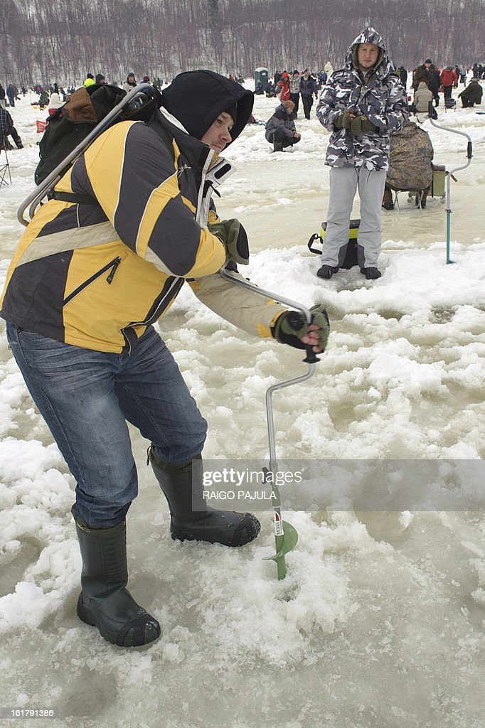 STORY - A man rotates a hole into the frozen lake as people take part in a fishing event in Viljandi, Estonia on February 16, 2013. More than 8,000 participants from different countries arrived for the fishing event.