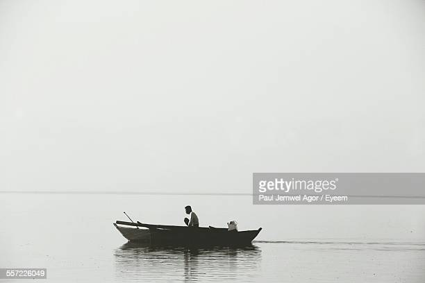 Man Rowing Boat In Sea