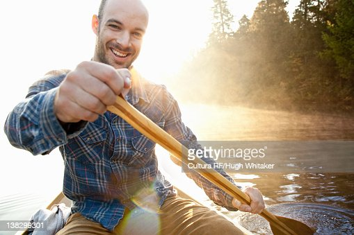 Man rowing canoe in still lake : Stock Photo