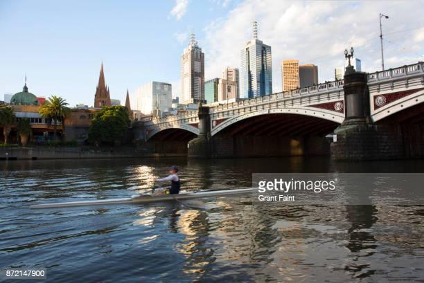 Man rowing on river near city.