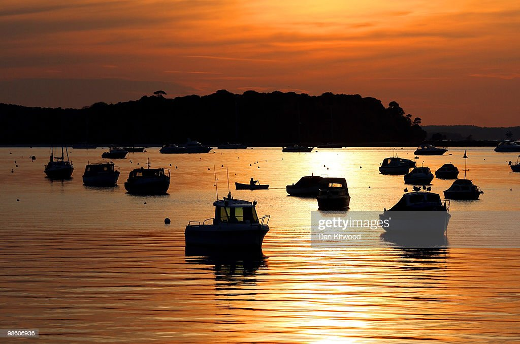A man rows a boat across Poole Harbour as the sun sets on April 21 2010 in Poole Dorset