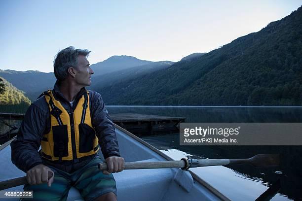 Man rows boat across tranquil lake, dawn