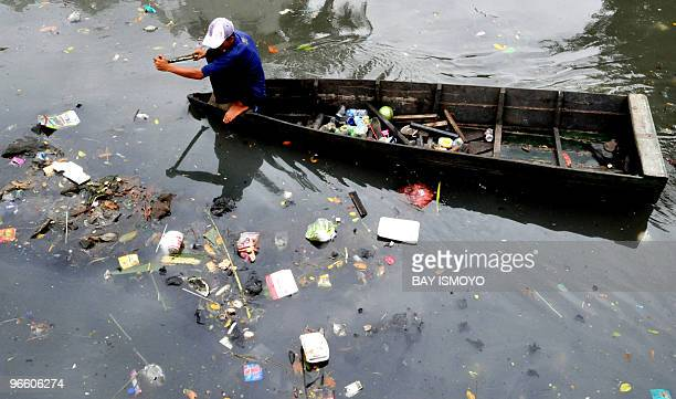 A man rows his craft through a dirty river in Jakarta on February 1 2009 as he looks for valuable waste that can be salvaged and sold on The global...