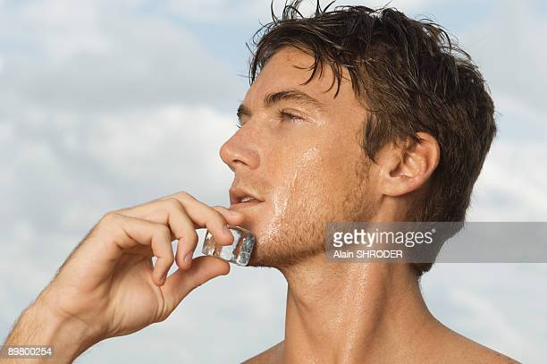 Man rubbing an ice cube on his face