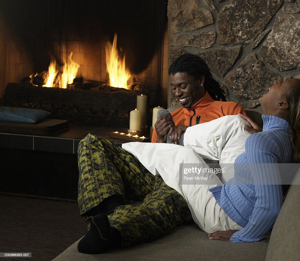 man and woman holding coffee cups on sofa beside fireplace