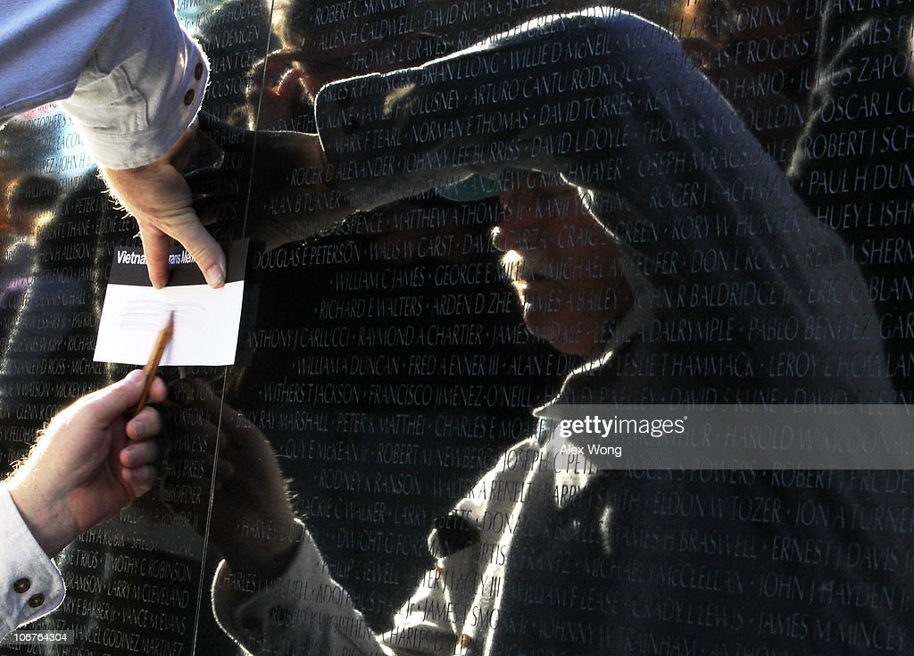 A man rubs a name from a wall of the Vietnam Veterans Memorial after a Veterans Day event November 11, 2010 in Washington, DC. The nation's veterans were honored and remembered during the annual Veterans Day.