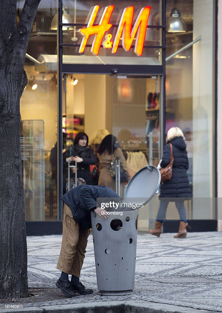 A man rummages through a public waste bin outside a Hennes & Mauritz AB (H&M) store in Prague, Czech Republic, on Sunday, Feb. 17, 2013. Worsened outlook for Czech economy is in line with the government's expectations and lower-than-planned tax revenue is 'manageable' under 2013 budget, Prime Minister Petr Necas said on Czech public television. Photographer: Martin Divisek/Bloomberg via Getty Images