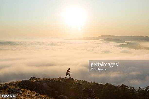 Man running above valley fog, Santa Tegra Mountain